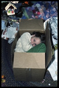 Thumbnail of Sequoya Frey nestled in a cardboard box at Christmas time, Montague Farm commune