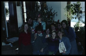 Thumbnail of Communards and children posed in front of the Christmas tree, Montague Farm commune Includes (rear row, l. to r.) Tony Mathews (with baby), Harvey Wasserman,             unidentified woman, Sam Lovejoy, unidentified man, Anna; front row (l. to r.):             Susan Kramer, Sequoya Frey, Janice Frey