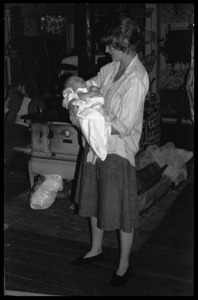 Thumbnail of Janice Frey holding an infant, Montague Farm commune