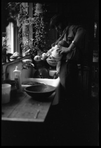 Thumbnail of Tony Mathews and baby at the kitchen sink, Montague Farm commune