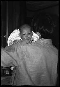 Thumbnail of Tony Mathews with a baby over his shoulder, Montague Farm commune