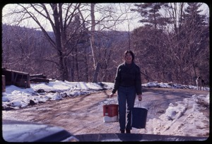 Thumbnail of Lise Finestone carrying sap buckets down the road while sugaring, Montague Farm             Commune