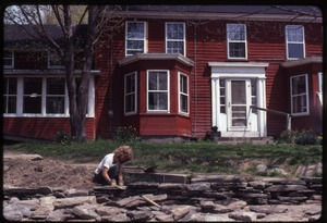 Thumbnail of Janice Frey setting a stone wall in front of the house, Montague Farm Commune