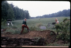 Thumbnail of Janice Frey (right) and Sue Kramer, digging in a flower bed by a stone wall, Montague Farm Commune