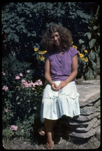 Thumbnail of Amy Wainer seated on a stone wall, Montague Farm Commune