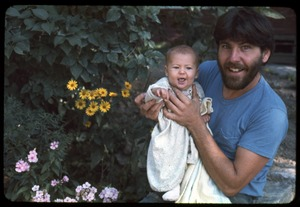 Thumbnail of Tony Mathews holding his infant daughter Phoebe, Montague Farm Commune