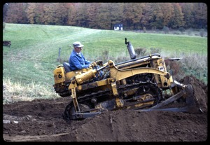 Thumbnail of Rob Ripley driving a bulldozer, Montague Farm Commune