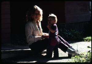 Thumbnail of Janice Frey seated with infant Phoebe Mathews, Montague Farm Commune