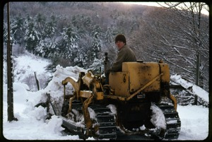 Thumbnail of Tony Mathews on a tracked tractor, clearing snow, Montague Farm Commune