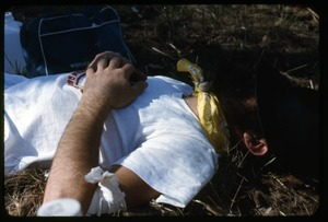 Thumbnail of Nap after arrival in camp: Occupation of the Seabrook Nuclear Power Plant Occupier napping on the ground, hat pulled over his eyes