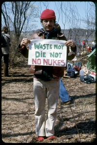 Thumbnail of In camp Josh Dostens: Occupation of the Seabrook Nuclear Power Plant Occupier holding a sign reading 'Waste not, die not. No nukes'
