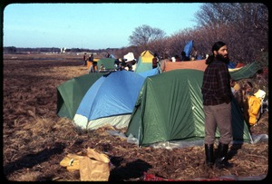 Thumbnail of Camp day 1: Occupation of the Seabrook Nuclear Power Plant Alan Berman standing in front of a row of tents