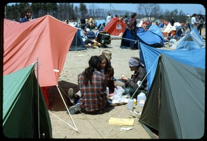 Thumbnail of Affinity group members eat together: Occupation of the Seabrook Nuclear Power Plant Occupiers huddled on the ground between tents, taking lunch