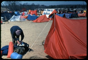 Thumbnail of Packing up [before arrest]: Occupation of the Seabrook Nuclear Power Plant Occupier stashing gear in backpack in front of tents (tent in the background             with large banner reading 'No more nukes')