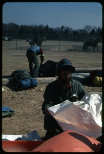 Thumbnail of Police arriving, packing up, Rick Stone: Occupation of the Seabrook Nuclear Power Plant Rick Stone in foreground packing up in preparation for arrest as mounted             police arrive in background