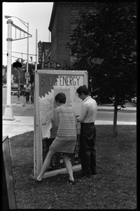 Thumbnail of Fran Koster and woman pinning things to a bulletin board at a solar energy demonstration, Greenfield Town Common