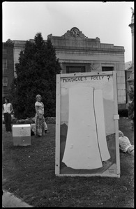 Thumbnail of Antinuclear protest on Greenfield town common, opposing the plan to build a             reactor in the town of Montague Sign reads: 'Montague's folly?': Nina Keller and Janice Frey in background