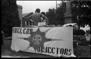 Thumbnail of Antinuclear protest on Greenfield town common, opposing the plan to build a             reactor in the town of Montague Sign reads: 'Nuclear objector' with image of a sunburst