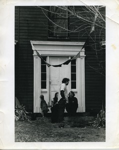 Thumbnail of Cathy Rogers, Ira Krasnik, and Michael Curry seated with a dog by the front door, Montague Farm Commune
