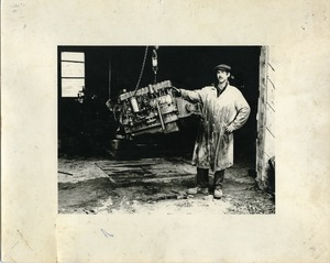 Thumbnail of Jim Aaron, posed with a suspended engine block, Montague Farm Commune