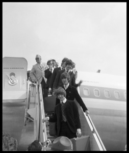 Thumbnail of Ringo Starr,  George Harrison, and Paul McCartney descending the ramp from a Pan             American airways Boeing 707 (John Lennon barely visible behind McCartney)