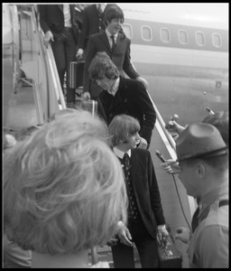 Thumbnail of Ringo Starr, George Harrison, and Paul McCartney descending the ramp from a Pan             American airways Boeing 707