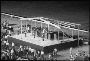 Thumbnail of The  Beatles performing at Suffolk Downs race track, police lined up in front of the             stage