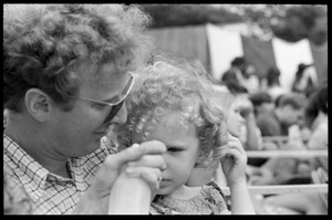 Thumbnail of Father and infant daughter in the audience, waiting to see Taj Mahal in concert, Newport Folk Festival