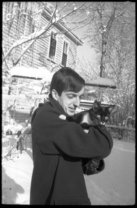 Thumbnail of Charles Frizzell holding a tuxedo cat outside after a heavy snow