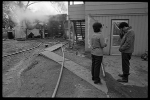Thumbnail of Man in anguish after learning that his garage was gutted by fire, and the family's cat was trapped inside Firefighters tending to the smoldering shed as man looks on