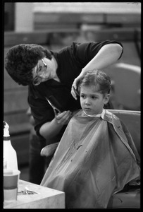 Thumbnail of Young boy in a barber chair, enduring a haircut