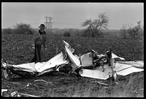 Thumbnail of Wreckage of a small engine plane crashed in a field during a tornado Policeman inspects the wreckage