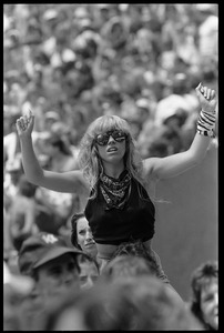 Thumbnail of A  fan gets a higher viewpoint via the shoulders of a friend during the Black             Sabbath set Woman in sunglasses, raising her arms at the Live Aid Concert, JFK Stadium