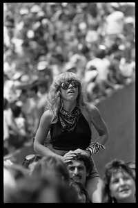 Thumbnail of A  fan gets a higher viewpoint via the shoulders of a friend during the Black Sabbath set Woman in sunglasses, seated on a friend's shoulders at the Live Aid Concert, JFK Stadium