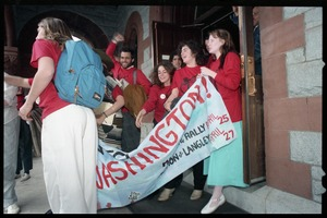 Thumbnail of Defendants exit the Hampshire County courthouse following their acquittal in the CIA             protest trial wearing 'Put the CIA on trial' t-shirts and carrying a banner reading 'On             to Washington' Amy Carter holding the left end of the banner