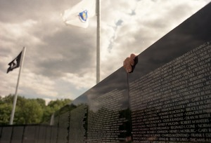 Thumbnail of Hand reaching over the moving Vietnam War memorial