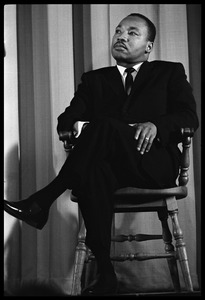 Thumbnail of Martin Luther King, Jr., waiting to speak at the Youth, Non-Violence, and Social Change             conference, Howard University Full-length portrait seated on stage in a Windsor chair