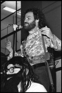 Thumbnail of Jerry Rubin, with bandolier and toy assault rifle slung over his shoulder,       addressing the audience at the microphone Yippie with a overflowing fake beard seated in front
