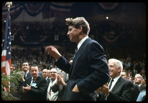 Thumbnail of Robert F. Kennedy on the campaign trail, walking into a packed auditorium, while         stumping for Democratic candidates in the northern Midwest