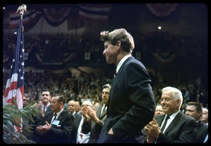Thumbnail of Robert F. Kennedy on the campaign trail, walking into a packed auditorium, while         stumping for candidates in the northern Midwest