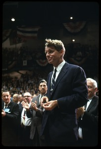 Thumbnail of Robert F. Kennedy on the campaign trail, walking into a packed auditorium while             stumping for Democratic candidates in the northern Midwest