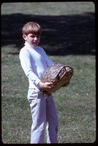 Thumbnail of Son of Robert F. and Ethel Kennedy standing on the lawn with a large tortoise