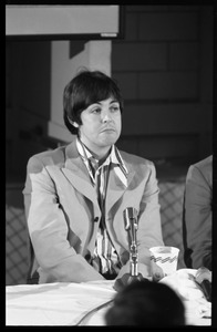 Thumbnail of Paul McCartney seated in front of a microphone at a table, during a Beatles press conference