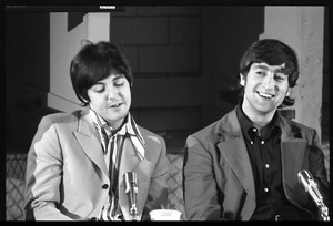 Thumbnail of Paul McCartney (left) and John Lennon seated at a table, during a Beatles press conference