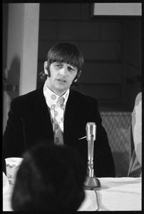 Thumbnail of Ringo Starr seated in front of a microphone at a table, during a Beatles press conference