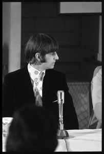 Thumbnail of Ringo Starr seated in front of a microphone at a table, in profile, during a Beatles press conference