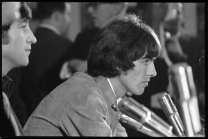 Thumbnail of George Harrison in front of a bank of microphones, in profile, during a Beatles press conference