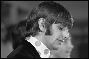 Thumbnail of Ringo Starr seated at a table during a Beatles press conference: close-up in             profile