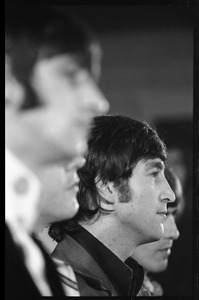 Thumbnail of John Lennon at a Beatles press conference, with Ringo Starr in the foreground             and George Harrison partly visible in the background