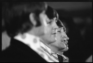 Thumbnail of Paul McCartney, John lennon, and George Harrison during a Beatles press conference, in profile: Ringo Starr in             foreground and John Lennon in the background